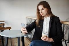 狩猎的时髦的博客作者新的照片的 坐在咖啡馆的可爱的女性城市探险家画象,采取selfie,当时 库存照片
