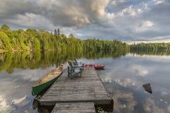 独木舟和皮船被栓对一个湖的一个船坞安大略的加拿大 免版税库存照片