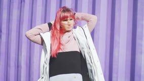 独立年轻女人画象有摆在紫色容器背景的桃红色头发的 t 股票视频