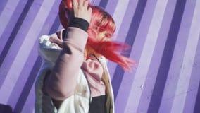 独立年轻女人画象有摆在紫色容器背景的桃红色头发的 t 股票录像
