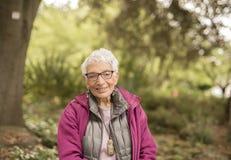 独立年长妇女在公园坐长凳 库存照片