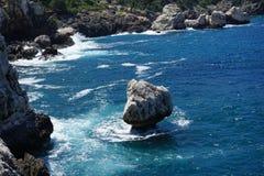 独立石头的看法在海,基地由波浪堆 免版税图库摄影