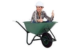 独轮车的女性工作者 库存图片