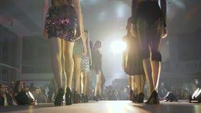 狭小通道在显示在阶段的时髦的褂子和时尚凉鞋塑造新的汇集衣裳在照明设备探照灯入 股票录像