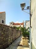狭窄和空的步行街道在老街市在克罗地亚 免版税库存照片