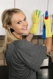 狭窄白肤金发的清洁碗柜的主妇 免版税库存照片