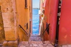 狭窄的石街道和罗维尼,克罗地亚普通建筑学  免版税库存照片