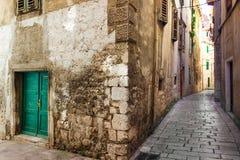 狭窄的老街道和围场在希贝尼克市,克罗地亚 免版税库存图片