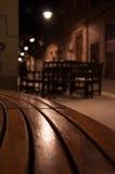 狭窄的街道和一条长凳在晚上 免版税库存图片