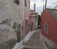 狭窄的街道和台阶有老红色房子和绿色门的,葡萄酒神色,科孚岛希腊 库存图片