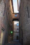 狭窄的街道和建筑连接两个大厦之间 意大利siena托斯卡纳 库存照片
