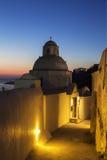 狭窄的街道在日落的与正统希腊教会,圣托里尼Fira镇 免版税图库摄影