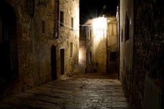 狭窄的街道在晚上在圣吉米尼亚诺在托斯卡纳,意大利 免版税库存照片