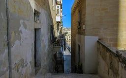 狭窄的街道在有大厦的瓦莱塔从黄色石灰石,马耳他,欧洲 库存照片