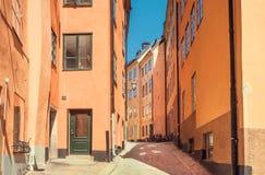 狭窄的街道在有窗口、被修补的石头和历史房子的老城市 斯德哥尔摩,瑞典视图 库存图片