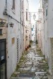 狭窄的街道在白色市奥斯图尼,普利亚,意大利 免版税库存图片