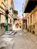 狭窄的街道,车道,有老房子的,在边的大厦在城市的一个恶劣的区域,贫民窟隧道 r 免版税库存照片