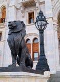 狮子后边黑雕塑和黑灯笼 免版税库存图片