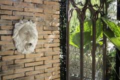 狮子头雕象在砖墙上的 免版税图库摄影