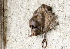 狮子有下面通道门环的` s头,在墙壁上在Gruyeres 免版税库存照片