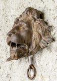 狮子有下面通道门环的` s头,在墙壁上在Gruyeres 免版税图库摄影