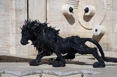狮子由老汽车轮胎做的艺术雕象在耶烈万小瀑布,亚美尼亚附近 免版税库存照片