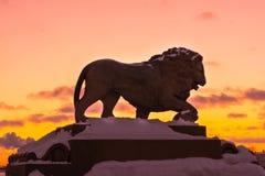 狮子的雕塑现出轮廓反对日落天空和云彩 免版税库存图片