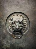 以狮子的头的形式古色古香的通道门环在老金属d 免版税库存照片