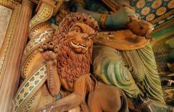 狮子雕塑和艺术品在18世纪寺庙有五颜六色的装饰的墙壁的 免版税库存图片