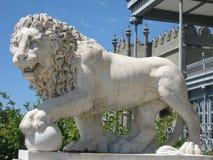 狮子雕塑由白色大理石制成反对老宫殿的背景 免版税库存图片