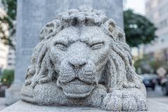 狮子顶头雕象城市环境squinning的眼睛力量安静g 库存图片