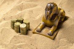 狮身人面象和硬币在沙子 图库摄影