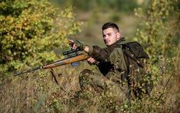 猎人举行步枪 男服伪装衣裳自然背景 寻找许可证 有胡子的严肃的猎人花费休闲 库存照片