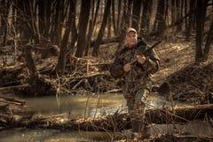 猎人人有猎枪的森林河在狩猎期期间 库存图片