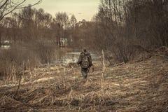 猎人人爬行在狩猎期期间的森林河 免版税图库摄影