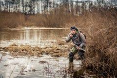 猎人人趟过通过沼泽的潜伏在灌木和展示打手势是安静的 库存图片