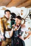 猎人和妇女一个高山山小屋的与垫铁 免版税库存照片