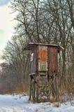猎人在相反的一边在一个领域在冬天森林里 免版税库存照片
