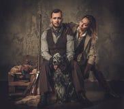 猎人夫妇与一把英国塞特种猎狗和猎枪在传统射击衣物,在黑暗的背景的开会的 库存照片