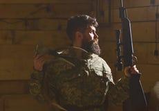 猎人概念 有胡子的现代猎人画象与他的战利品的拿着步枪 有胡子的人穿伪装衣物 库存图片