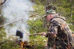 猎人烹调在营火 库存图片