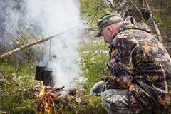 猎人烹调在营火 免版税库存照片