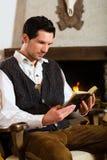 猎人的客舱的年轻人读圣经的 图库摄影