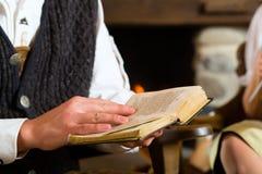 猎人的客舱的年轻人读圣经的 库存照片