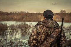 猎人调查在伪装的距离天际的人狩猎在狩猎期背面图日落河洪水风景期间 图库摄影