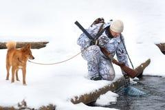 猎人采取从河的水冬天狩猎的 库存照片