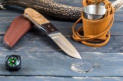 猎刀、玻璃和指南针 库存照片