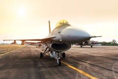猎鹰喷气式歼击机军用飞机在日落的跑道停放了 图库摄影