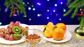 猕猴桃、葡萄和坚果用蜂蜜和在桌上与一个装饰的圣诞树球和光模糊的bokeh 影视素材
