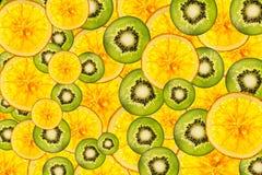猕猴桃桔子混合被点燃的五颜六色的被切的果子背景 免版税库存照片